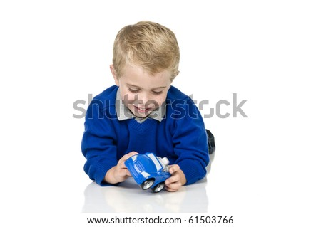 3 yrs old boy playing with a plastic car, shot on white reflective surface, room for copy