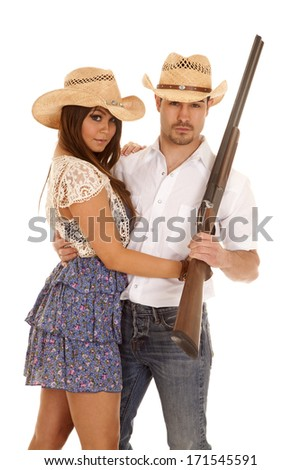 A a cowboy and cowgirl holding on to each other and he is holding on to a rifle. - stock photo