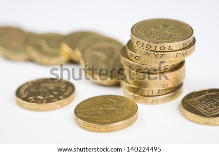 A a toppled pile of pound coins on a table. - stock photo