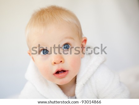 A adorable sweet baby boy with blue innocent eyes gazes at the camera.  This studio shot is taken against a white background. - stock photo