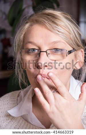 A adult caucasian woman licking her finger - stock photo