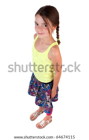 A 9 (almost 10!) year old girl with long brown hair standing and looking up at the camera. - stock photo