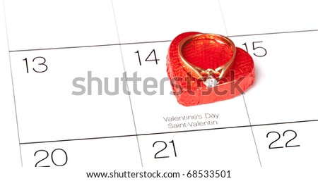 A angled side view of a red heart shaped chocolate candy with an engagement ring on top marking February 14th on the calendar.
