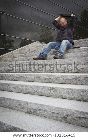 A angry man bites his computer / laptop in the stairs. - stock photo