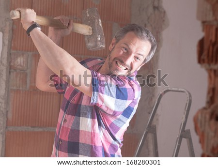A angry man on a building site has a big hammer to damage a wall. - stock photo