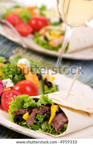 A appetizing beef steak and chicken wrap with lots of vegetables and a side salad. - stock photo