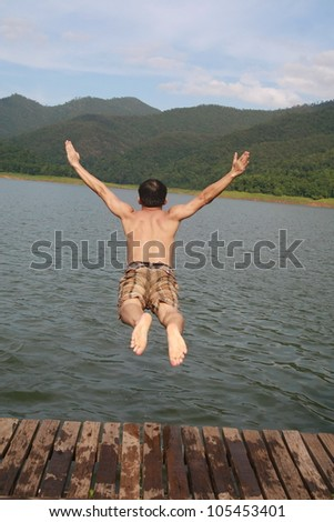 a asia man jump to lake water with mountain view background - stock photo