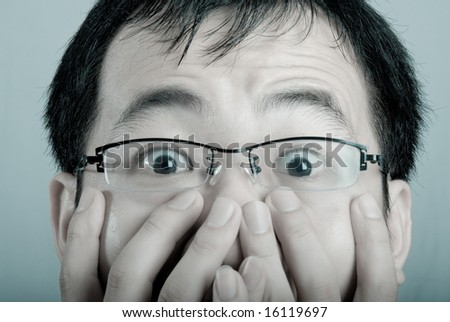 A asian business man shows a surprised expression with his hands covering his mouth in cold tone. - stock photo