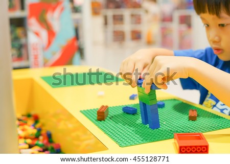 A asian child playing with lots of colorful plastic blocks indoor. Active kid boy having fun with building and creating concept, selective focus left hand - stock photo