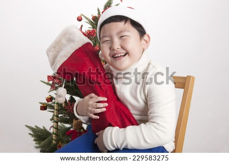 A asian(korea, japan, chinese, china) boy hold(hug) christmas socks for presents and wearing christmas hat with big smile isolated white at the studio and christmas tree. - stock photo