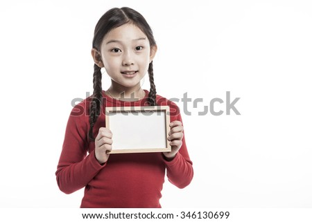 A asian(korean, japanese, chinese) girls(kid, student, child, woman, female) wearing red shirts and blue denim hold a empty(blank) photo frame isolated white. - stock photo