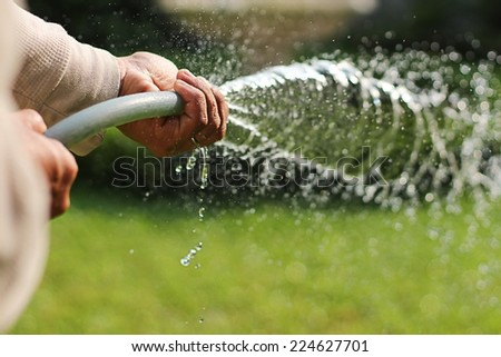 A asian man watering the garden on sunny day - stock photo