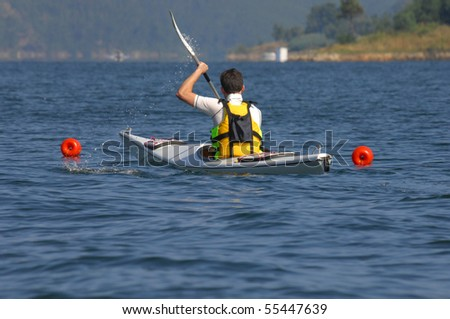 A athletic man kayaking on lake - stock photo