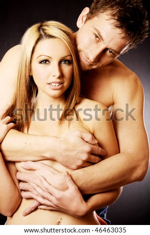 A attractive loving couple topless and cuddling in front of a dark background.
