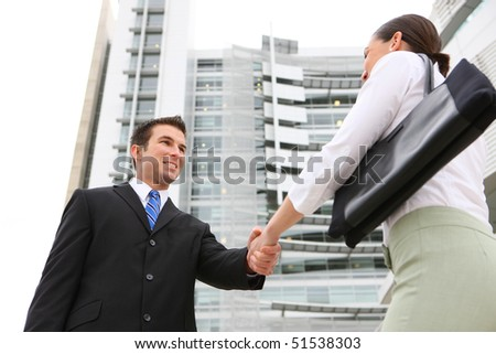 A attractive man and woman business team handshake at office building