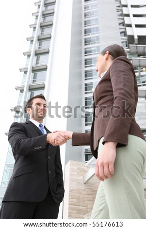 A attractive man and woman business team handshake at office building - stock photo
