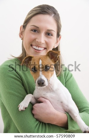 A attractive young woman is wearing a green sweater and smiling while holding a dog. Vertical shot. - stock photo