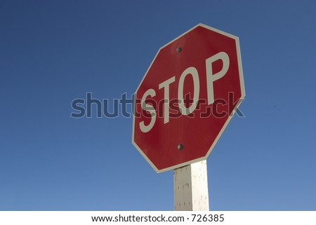 A authoritatively low angle view of stop sign against a very blue sky.