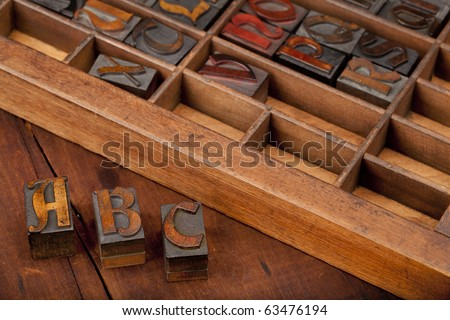 A, B and C letters in vintage wooden letterpress type (Abbey typeface) with old typesetter case in background, image can be flipped in horizontal for original view of printing blocks - stock photo
