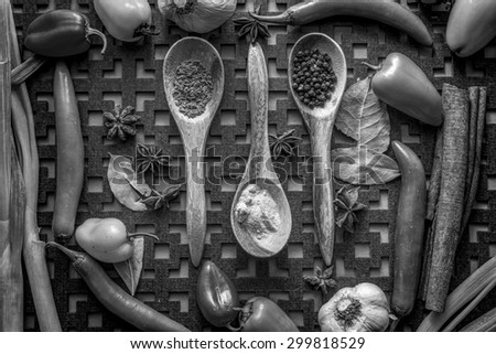 A B&W of an assortment of veggies and spices and three wooden spoons. - stock photo