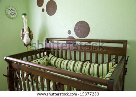 A babies room with green walls and brown dots. - stock photo