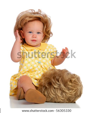 A baby adjusting her wig. - stock photo
