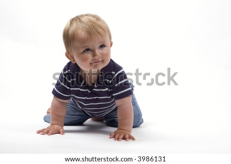 A baby boy in a striped top learns to crawl - stock photo