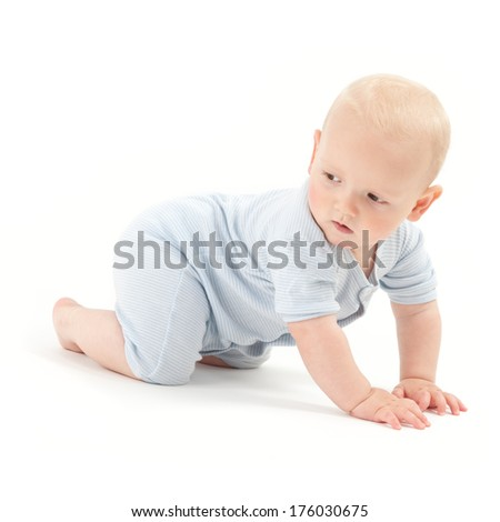 A baby boy is crawling and looking behind him.