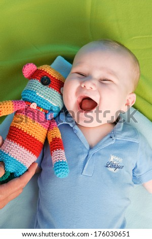 A baby boy laughing with a stuffed animal. - stock photo