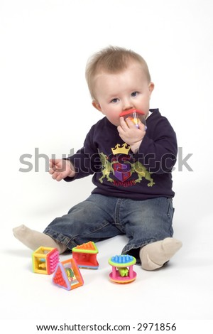 A baby boy pays with some stackable shaped blocks against a white background - stock photo