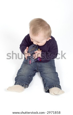 A baby boy plays with a calculator against a white background - stock photo