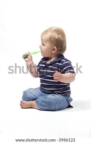 A baby boy plays with his first toothbrush against a white background - stock photo