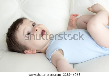 A baby boy relaxing in sofa at home