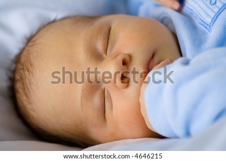 A baby boy sleeping in blue. - stock photo