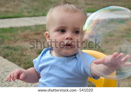 a baby boy trying to touch a bubble - stock photo