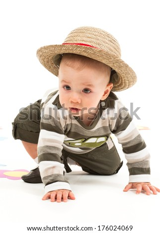 A baby boy, who looks as if he is trying to stand. - stock photo