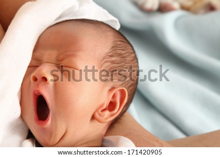 A baby boy yawning - stock photo