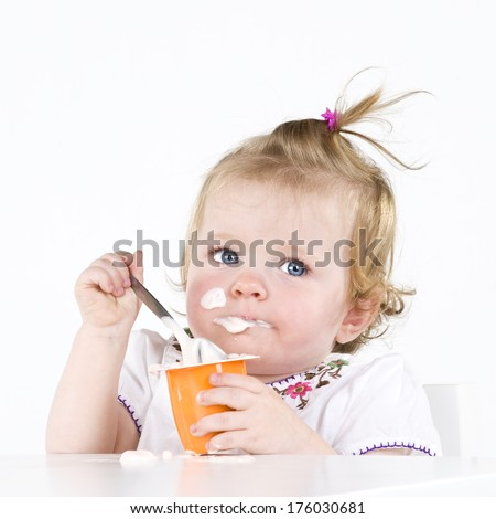 A baby eating yogurt with some on her face. - stock photo