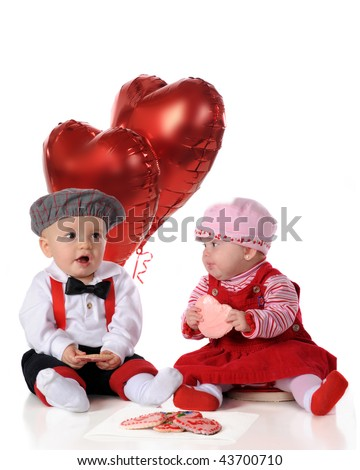A baby girl and boy, dressed for a big date, snacking on heart-shaped cookies together.  Isolated on white. - stock photo