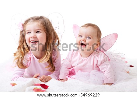 A baby girl and her older sister lie on the ground in fairy outfits.  Horizontal shot. - stock photo