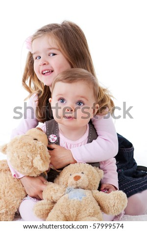 A baby girl and her older sister sitting with teddies. Vertical shot. - stock photo