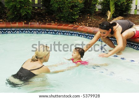 A baby girl at swimming lessons.