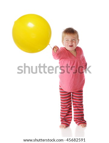 A baby girl delightedly playing with a big, yellow punch ball.  Isolated on white. - stock photo
