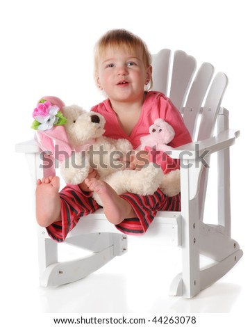 A baby girl happily sitting in an Adirondack rocking chair with her stuffed mama and baby bear on her lap.  Isolated on white. - stock photo