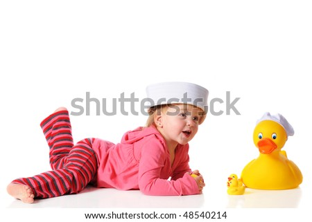 A baby girl in a sailor hat playing with a large duck, also in a sailor hat, and its ducklings.  Isolated on white. - stock photo
