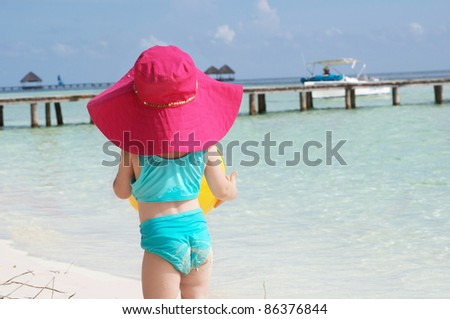 a baby girl in her sun hat on the beach - stock photo