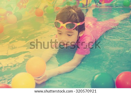 A baby girl in pink suit playing water and balls in blue kiddie pool - vintage effect