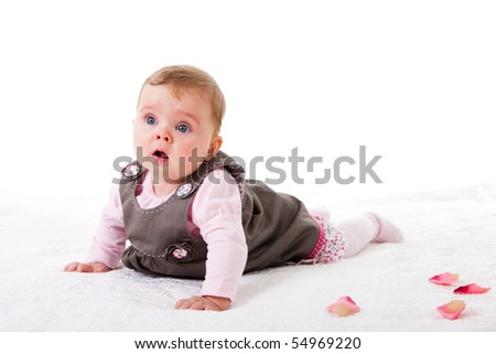 A baby girl is crawling along a floor with flower petals.  Horizontal shot.