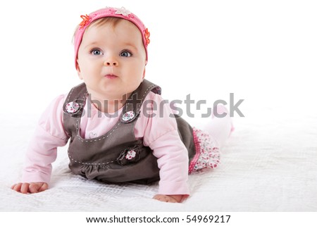 A baby girl is crawling along the floor with an inquisitive look on her face.  Horizontal shot. - stock photo