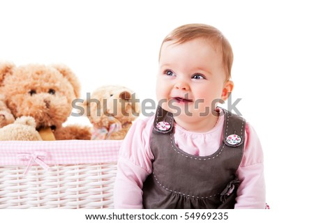 A baby girl is sitting next to a basket of teddy bears and smiling.  Horizontal shot.